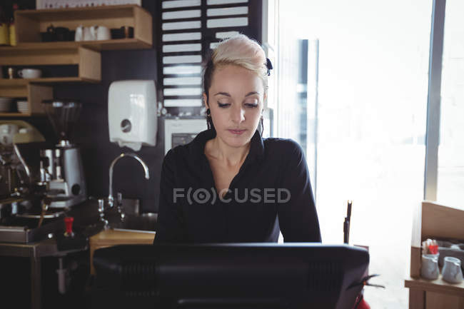 Waitress using cash register at counter in cafe — Stock Photo
