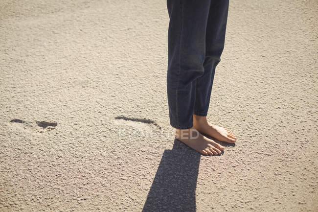 Partie basse d'une femme debout sur le sable de la plage — Photo de stock
