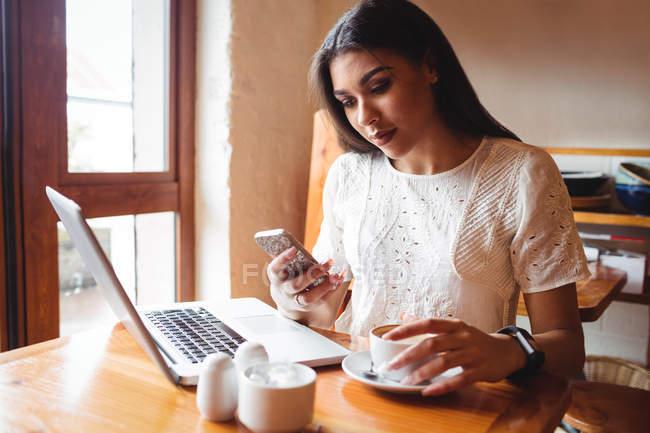Belle femme utilisant un téléphone portable tout en prenant une tasse de café au café — Photo de stock