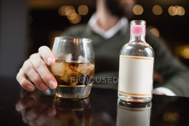 Male hand with glass of drink and small liquor on table in bar — Stock Photo