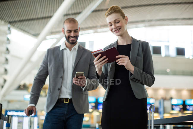 Деловые люди ждут в очереди у стойки регистрации с багажом в терминале аэропорта — стоковое фото