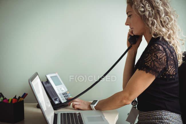 Businesswoman talking on landline in office — Stock Photo