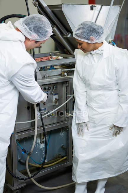 Techniciens examinant la machine de traitement de la viande à l'usine de viande — Photo de stock