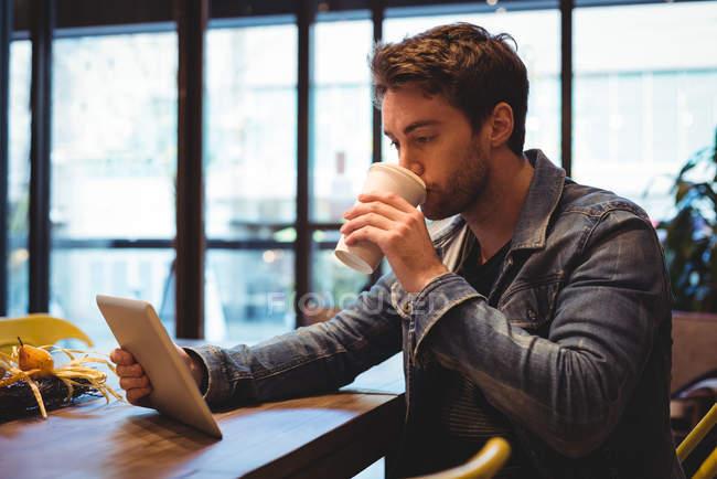 Homem usando tablet digital enquanto toma café no café — Fotografia de Stock
