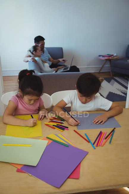 Garçon et fille dessin en papier tandis que les parents en utilisant un ordinateur portable en arrière-plan à la maison — Photo de stock