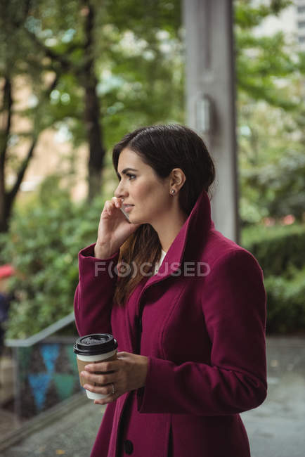 Side view of businesswoman holding disposable coffee cup and talking on mobile phone — Stock Photo
