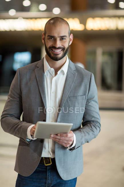 Retrato de hombre de negocios sonriendo con tableta digital en sala de espera en terminal del aeropuerto - foto de stock