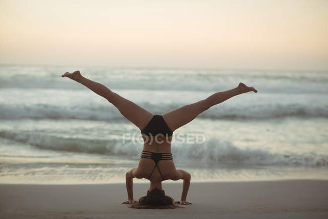 Woman performing headstand on beach at dusk — Stock Photo