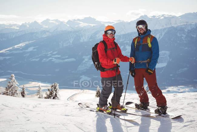 Два лыжников, стоя вместе на заснеженные горы в зимнее время — стоковое фото