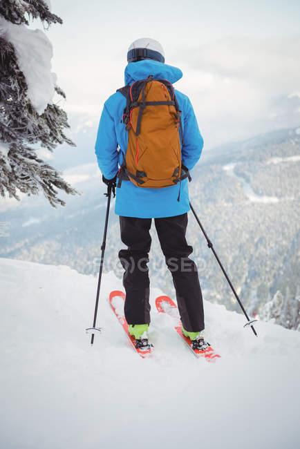 Vista traseira do esquiador, esqui na neve coberto montanhas — Fotografia de Stock