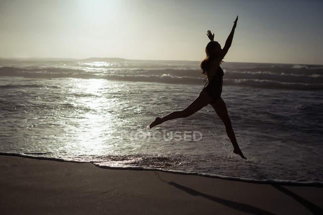 Woman jumping on beach at dusk — Stock Photo