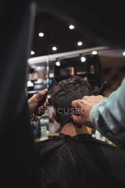 Hombre consiguiendo pelo recortado por estilista con maquinilla de afeitar en peluquería - foto de stock