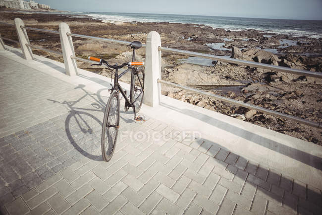 Bicyclette appuyé par rampe promenade près du rivage de la mer — Photo de stock