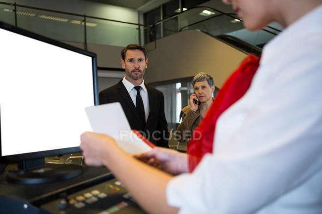 Close-up of female staff checking boarding pass with passengers in background — Stock Photo
