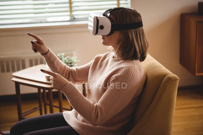 Woman using virtual reality headset glasses at home — Stock Photo