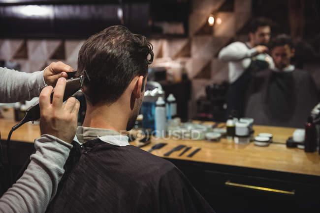 Uomo ottenere capelli tagliati da stilista con trimmer in negozio di barbiere — Foto stock