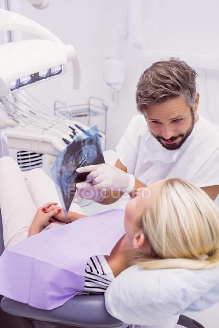 Odontoiatra che mostra i raggi X alla paziente in clinica — Foto stock