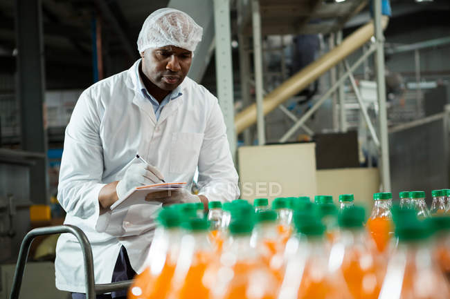 Serious male worker noting in juice factory — Stock Photo
