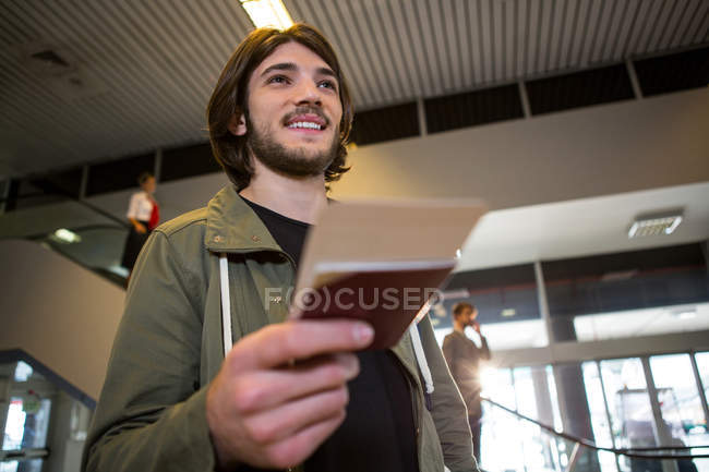 Happy man receiving passport and boarding pass at airport terminal — Stock Photo