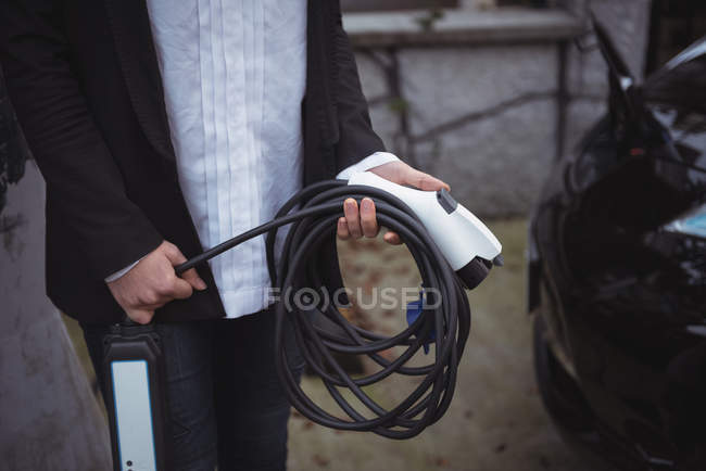 Mid section of woman holding car charger at electric vehicle charging station — Stock Photo