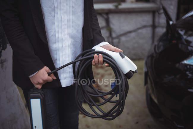 Partie médiane de la femme tenant le chargeur de voiture à la station de charge du véhicule électrique — Photo de stock