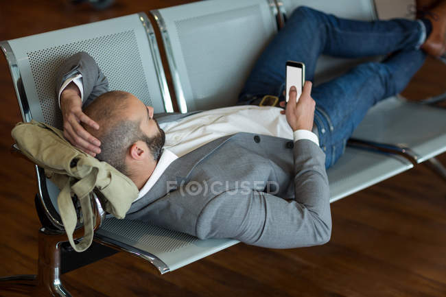 Businessman using mobile phone while lying on chairs in waiting area at airport terminal — Stock Photo