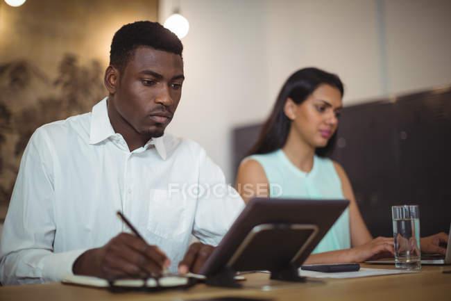 Hombre de negocios y un colega que trabaja en su escritorio en la oficina - foto de stock