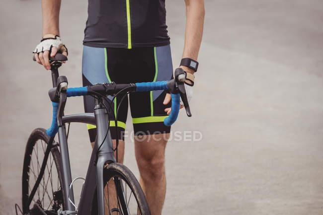 Середньої частини спортсмена, стоячи з велосипеда — стокове фото