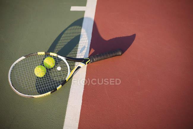Primer plano de la raqueta de tenis y pelotas en cancha - foto de stock