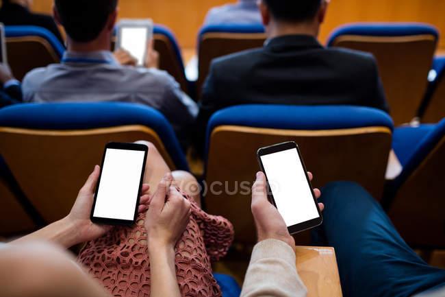 Executivos de empresas que participam de uma reunião de negócios usando telefone celular no centro de conferências — Fotografia de Stock