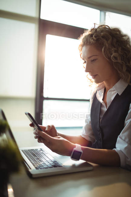 Female business executive using mobile phone while working on laptop in office — Stock Photo