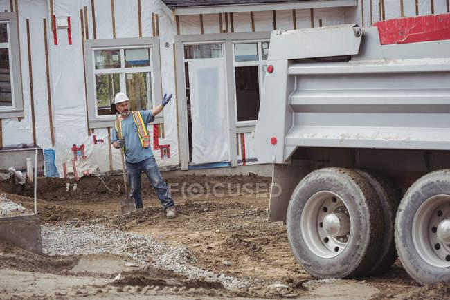 Працівник будівництва, стоячи на будівельному майданчику Самоскид — стокове фото