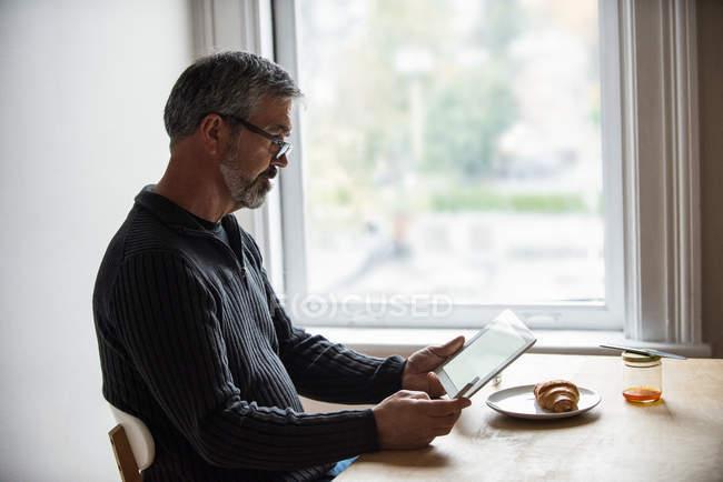 Людина за допомогою цифрових планшетів і мобільний телефон вдома — стокове фото