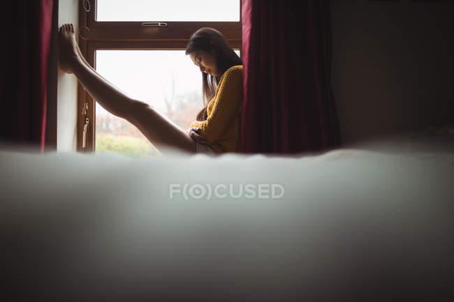 Mujer sentada en el alféizar de la ventana y mirando hacia abajo en el hogar - foto de stock