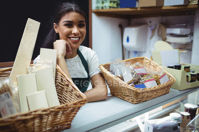 Female staff smiling at food counter in supermarket — Stock Photo