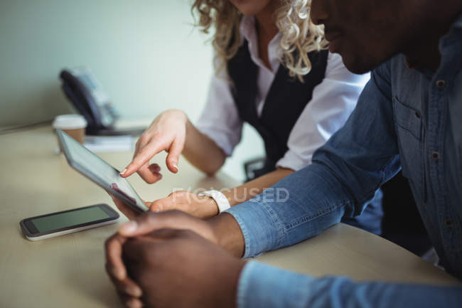 Close-up of business executives discussing over digital tablet in office — Stock Photo