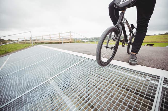 Велогонщик, стоящий на велосипеде BMX на стартовой рампе в скейтпарке — стоковое фото