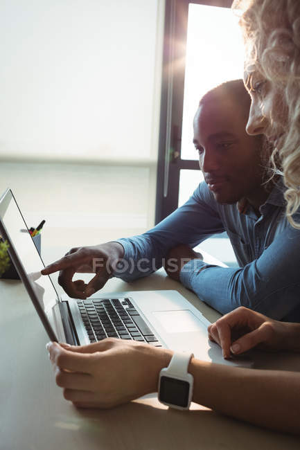 Business executives discussing over laptop in office — Stock Photo