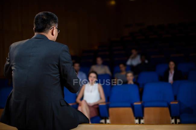 Visão traseira do executivo masculino de negócios conversando com colegas no centro de conferências — Fotografia de Stock