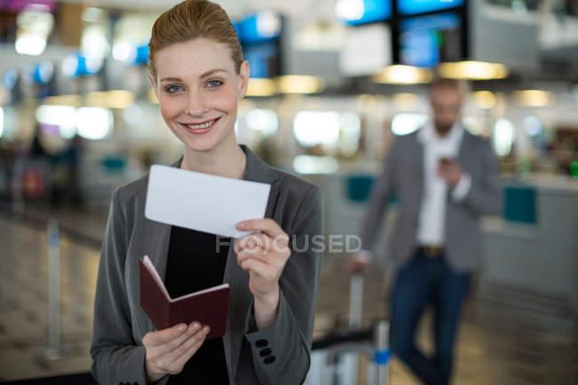 Retrato de una mujer de negocios sonriente mostrando su tarjeta de embarque en la terminal del aeropuerto - foto de stock