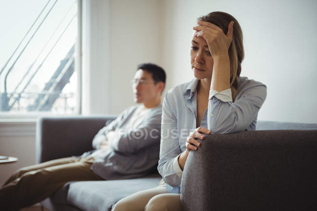 Upset couple sitting on sofa and ignoring each other - foto de stock