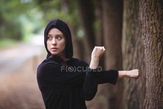 Femme effectuant exercice d'étirement dans la forêt — Photo de stock