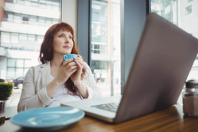 Pregnant businesswoman having coffee in office cafeteria — Stock Photo