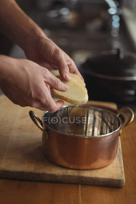 Close-up of hands of man putting potato slices in to stew pot in kitchen — Foto stock