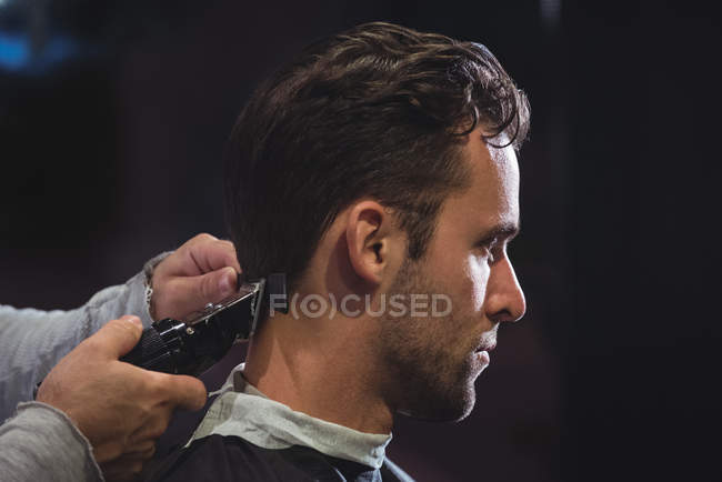 Cliente conseguir pelo recortado con trimmer en peluquería - foto de stock