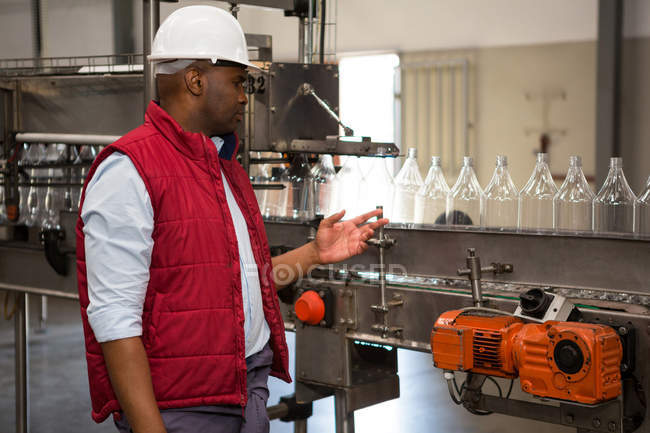 Confident male operator monitoring bottles on production line in juice factory — Stock Photo