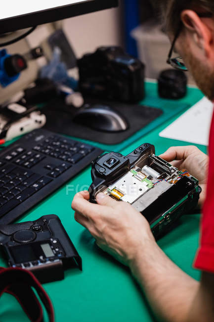 Man repairing digital camera in repair shop — Stock Photo