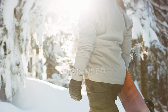 Mid section of woman standing and holding a snowboard on snow covered mountain — Stock Photo
