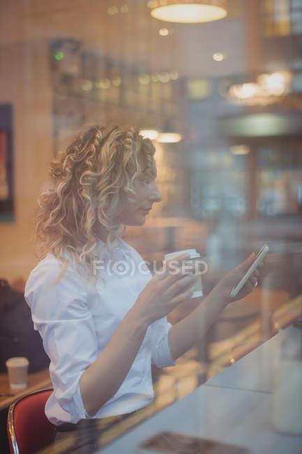 Femme réfléchie assise avec un café au comptoir à la cafétéria — Photo de stock