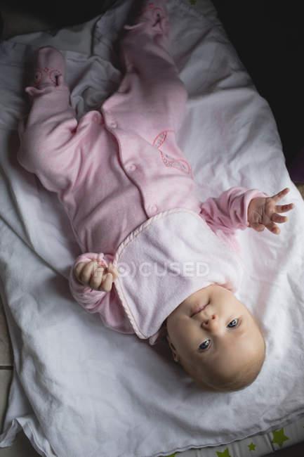 Nahaufnahme eines niedlichen Babys, das zu Hause auf einem Bettlaken liegt — Stockfoto